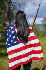 Back of Woman Wearing American Flag, Holding Rifle in Hand