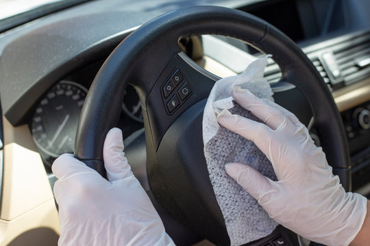 Hands with glove wiping car steering wheel