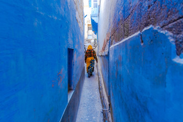 Indian women in traditonal india dressed Indian Saree walking through the narrow blue streets of the blue city of Jodhpur, Rajasthan, India.