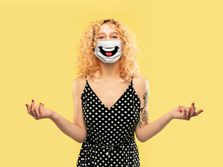 Happy laugh. Portrait of young caucasian woman with emotion on her protective face mask isolated on...