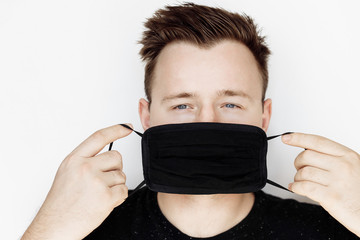 European attractive man wear black medical mask on the white background. Protection from coronavirus. Papier Peint