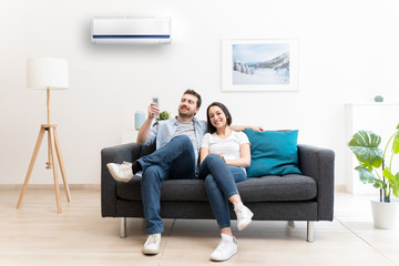 Happy couple cool down using air conditioning at home