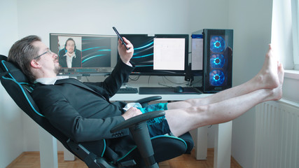Man wearing business suit on video call from home in shorts