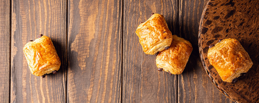 Food background with freshly baked sweet buns puff pastry with chocolate on old wooden table. Breakfast or brunch concept with copy space, top view