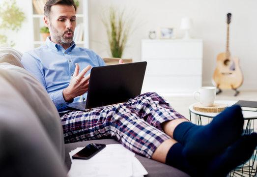 Man working on computer and wearing pajamas