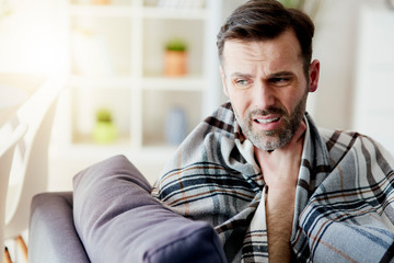 Man with a sore throat staying at home