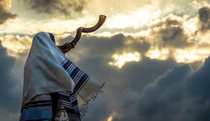 Jewish man in a tallith prayer shawl against dramatic sky