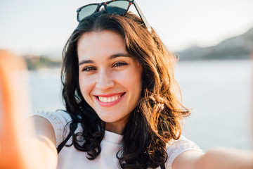 Happy beautiful young woman making a selfie by the sea in summer Fotomurales