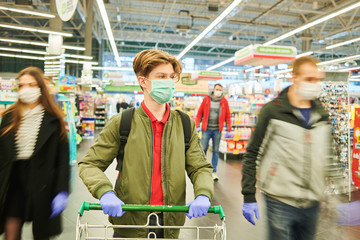 man in mask and protective gloves buying in shop at coronavirus epidemic