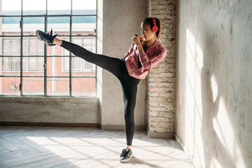 Young beautiful asiatic woman indoors at home training boxing listening music