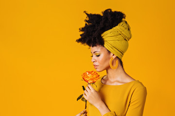 Profile portrait of a beautiful young woman smelling yellow orange rose and looking down, isolated on yellow background
