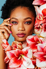 Portrait of a beautiful young woman with pink make up, lips, nail polish and amaryllis flower blooms around face