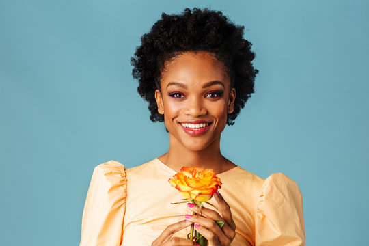 Profile portrait of a happy young woman holding yellow orange rose and smiling, isolated on blue background