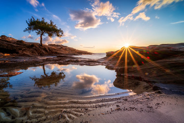 Magnificent sunset view with sun rays and beautiful reflections at the rocky coastline of Thasos...