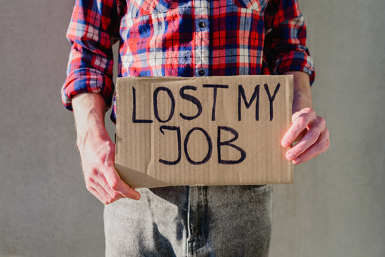 Man worker in plaid shirt with cardboard sign LOST JOB. Jobless, unemployment concept. Asking for money