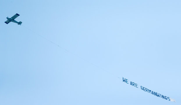 A small airplane pulls a banner while flying over the Lufthansa headquarters in Frankfurt