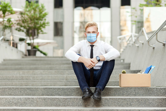 Losing job. Unfair worker with surgical medical mask sitting on stair and seriosly looking at camera. Outdoor shot. business crisis, working and health care concept.
