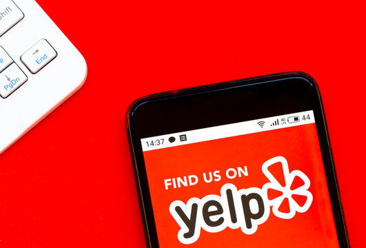 In this photo illustration Yelp logo is seen displayed on a smartphone
