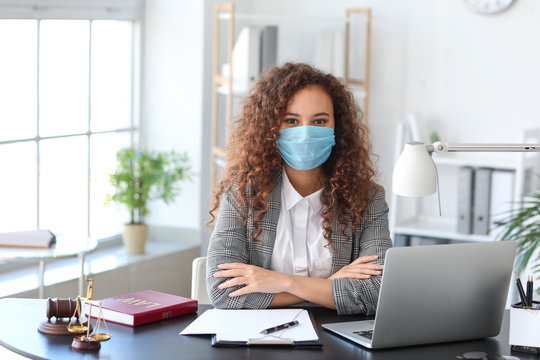 Female lawyer in protective mask working in office
