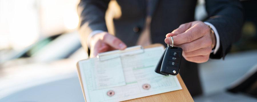 Autokauf, Verkäufer hält Zulassung Papiere und Schlüssel vor einer Reihe an Neuwagen