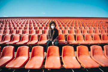 Curly girl in a surgical mask sitting in an empty stadium during epidemic disease Covid-19. Fotobehang