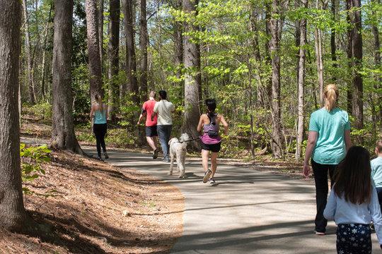 Visitors to Lake Johnson walk and jog along trails while practicing social distancing among the COVID-19 epidemic.