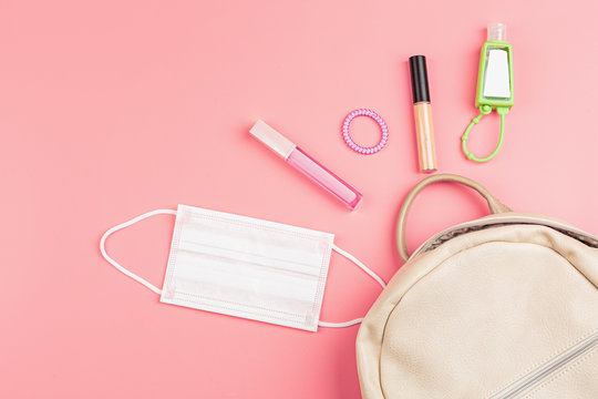 Flat lay of leather woman bag open out with face mask, sanitizer hand gel to protect from Coronavirus or COVID-19, lipstick, accessories on pink background with copy space.