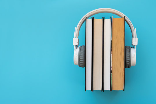 White headphones with stack of books on blue background. Audio books or modern education concept