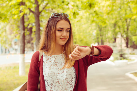 Woman happy smiling looking at wristwatch isolated on green park background