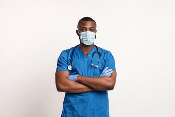 Confident black doctor in face mask and gloves over white Fotoväggar