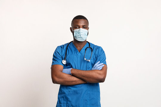 Confident black doctor in face mask and gloves over white