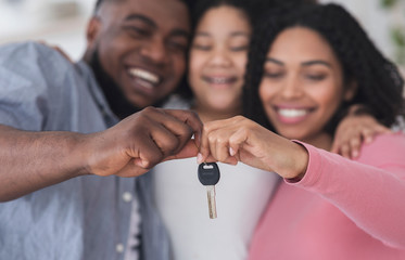 Smiling black family of three holding keys from their new flat