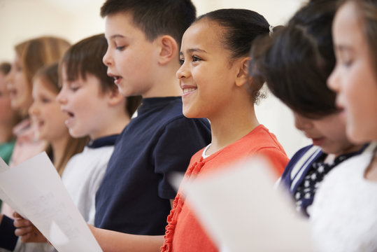 Group Of School Children Singing In Choir At Stage School Together