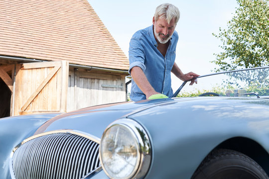 Mature Man Polishing Restored Classic Sports Car Outdoors At Home