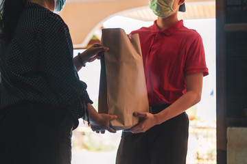 Delivery personnel deliver goods to customers during the covid-19 virus epidemic around the world,Therefore must wear a mask to prevent the spread of the disease,Express delivery . Quarantine