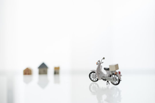 Stay home, Shelter in Place with Delivery and shopping online Concept. Close up of scotter / Motorcycle with container box and mini house as background.
