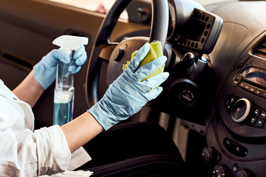 Car disinfecting service. Cleansing car interior and spraying with disinfection liquid