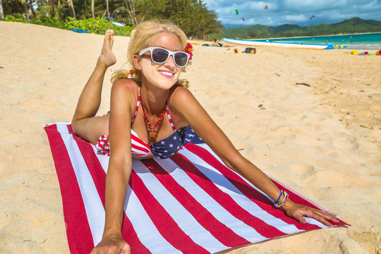 Suntan face sign during Covid-19 pandemic. White face for using a sanitary mask on woman with American flag towel in Hawaiian Lanikai Beach, with American flag bikini in Oahu island of Hawaii, USA.