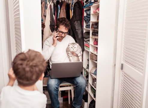 Busy father trying to find a quiet place in a wardrobe between clothes  to hide from children for a work at the laptop. Work from home. Home office. Quarantine. Freelancer.