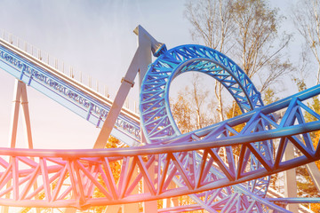 Loop and turn on a blue roller coaster in an amusement park Fotobehang