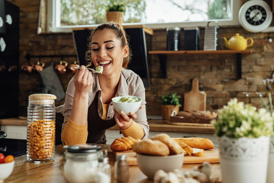 Smiling woman tasting food while cooking in the kitchen.