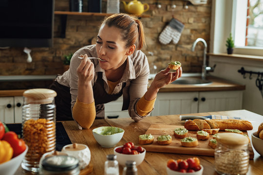 Young woman eating while making avocado bruschetta in the kitchen.