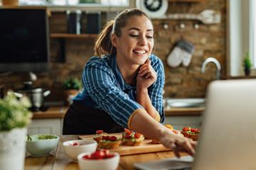 Happy woman surfing the net on laptop while preparing bruschetta in the kitchen.