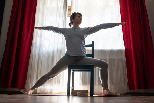 Young yoga woman doing warrior pose using chair.