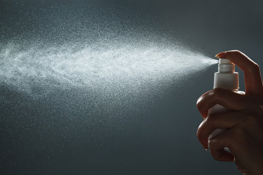 Close-up view of human hand and antiseptic spray bottle on dark background. Control Epidemic Prevention measures of coronavirus.