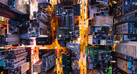 Aerial top view of downtown district  buildings in night city light. Bird's eye view from drone of cityscape metropolis infrastructure, crossing streets with parked cars. Development infrastructure Fotomurales