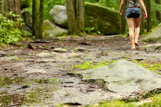 Woman walking barefoot through a forest with a rocky floor.