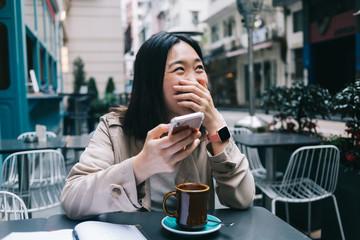 Cheerful Asian woman browsing smartphone in cafe Fotobehang