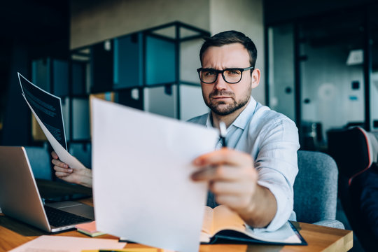 Frowned man working in office with documents