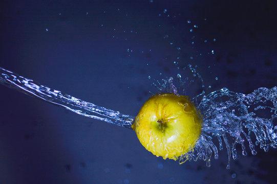 Close-up Of Water Splashing On Apple